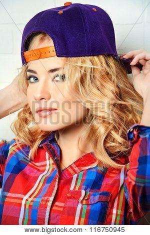 Beautiful modern girl with curly blonde hair wearing baseball cap and checkered shirt posing by a brick wall.