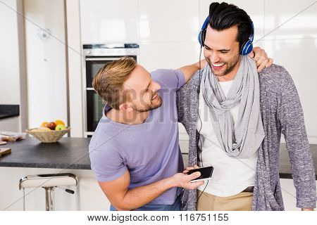 Smiling gay couple listening to music in the kitchen