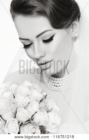 Black and white portrait of young beautiful bride with winged eyes make-up
