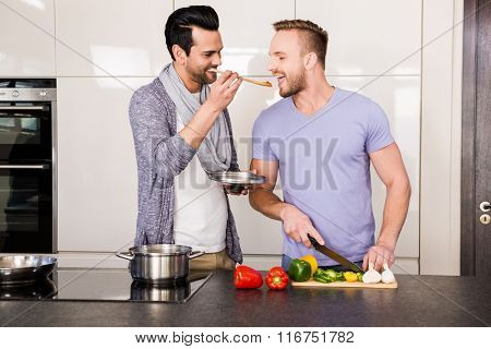Smiling man tasting food in the kitchen