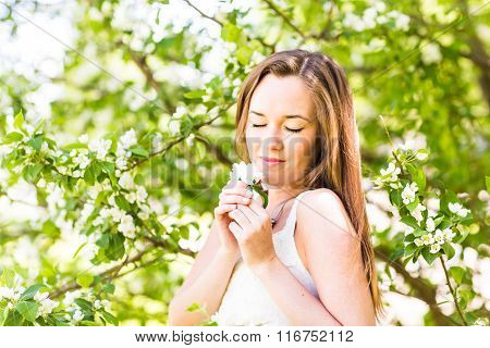 Romantic young woman with closed eyes in the spring garden among apple blossom, soft focus