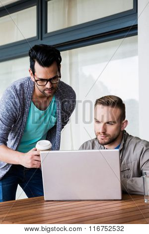 Focused gay couple using laptop outdoors