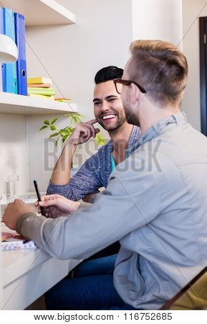 Happy gay couple discussing in office
