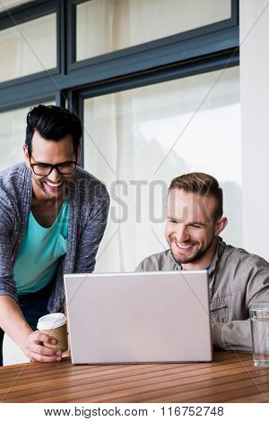 Happy gay couple using laptop outdoors