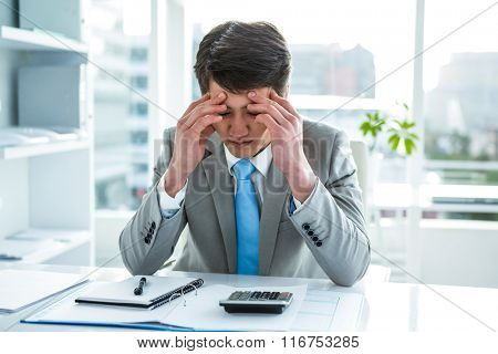 Troubled asian businessman in his desk holding his head