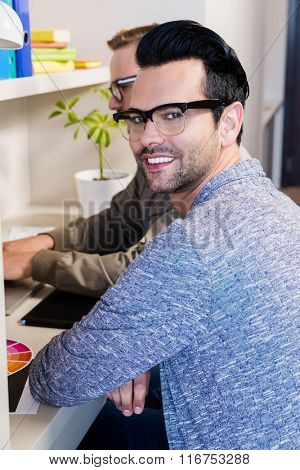 Happy gay couple working together in office