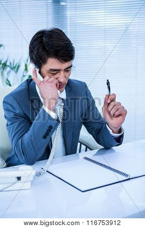 Asian businessman talking on the telephone in his office