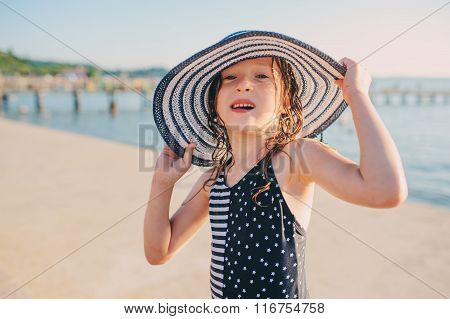 happy child in swimsuit relaxing on the summer beach and getting some tan. Warm weather cozy mood.