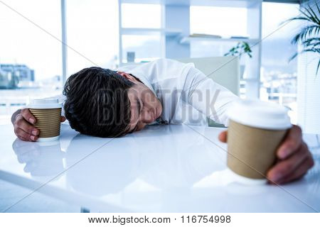 Sleeping businessman holding goblet of coffee lying on his desk