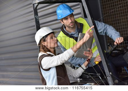 Warehouseman driving cart, listening to operator instructions