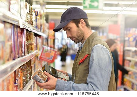 Sales assistant scanning products before putting for sale