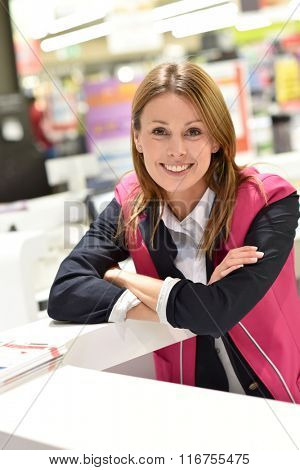 Customer service woman standing at the reception desk of supermarket