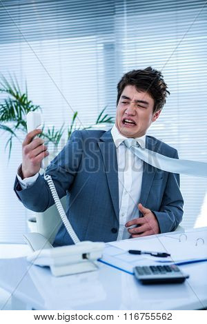 Angry asian businessman shouting on the phone in his office