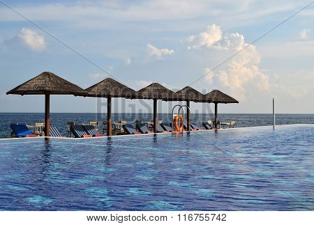 Swimming Pool With Sunchairs And Natural Umbrellas