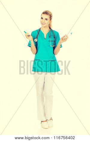 Smiling female nurse with two syringes in the hands