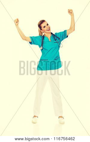 Young happy female doctor with hands up