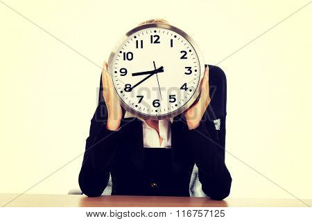 Businesswoman hidden behind the clock