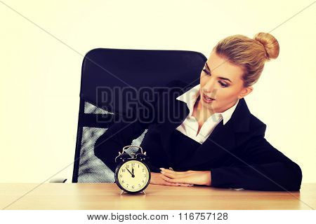 Surprised businesswoman looking at alarm clock behind the desk