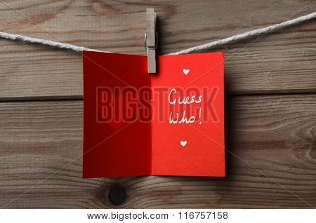 Red Valentines Day Card Pegged To String On Wood Background