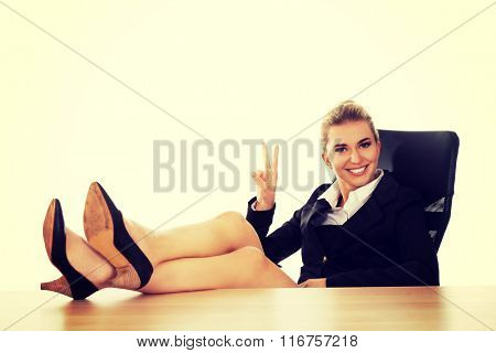 Happy young businesswoman holding legs on the desk