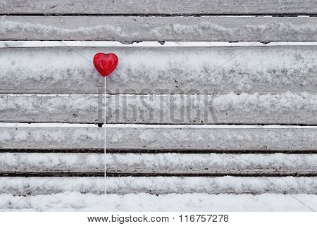 Red lollipop heart shaped on the bench