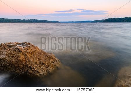 Rocky Shoreline Of A Lake At Sunset