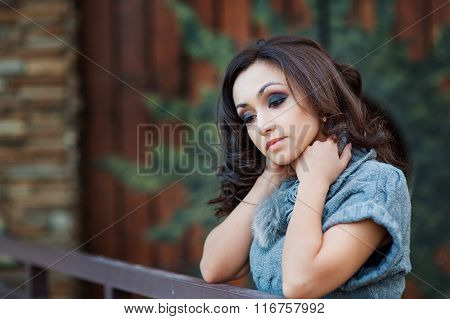 Beautiful Woman In A Gray Knitted Sweater Leaned On The Railing