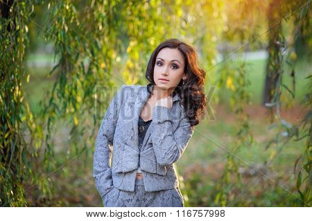 Beautiful Woman In A Gray Suit Walking In The Spring Park