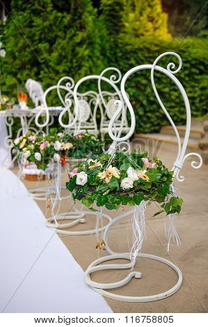 Decor Of The Wedding Flowers In Baskets Hanging On A Metal Stand