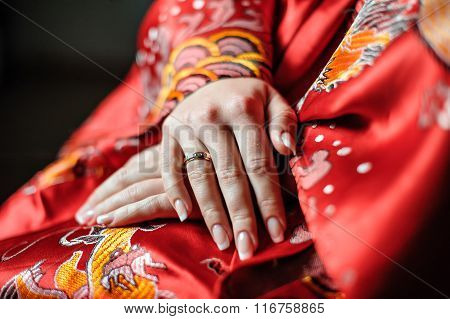 Hands Of A Bride In A Red Robe With A Wedding Ring On Her Finger