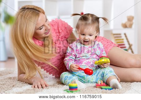 Baby playing with her mother on carpet in nursery