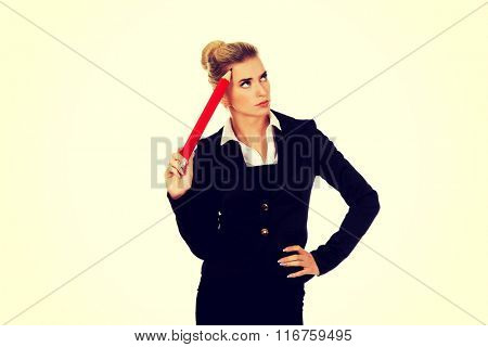 Young businesswoman thinking with big pen