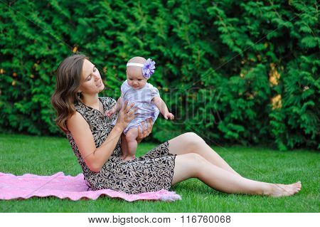 Happy Mother And Little Baby Girl Resting In The Summer Garden