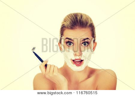 Young shocked woman shaving her face with a razor