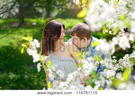 Man Kisses A Woman's Shoulder In A Spring Garden