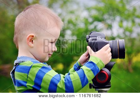 Pretty Boy Shooting With Camera On Meadow In Spring