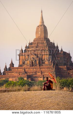 novice monk with red umbrella walking in front of Sulamani Pagodas.