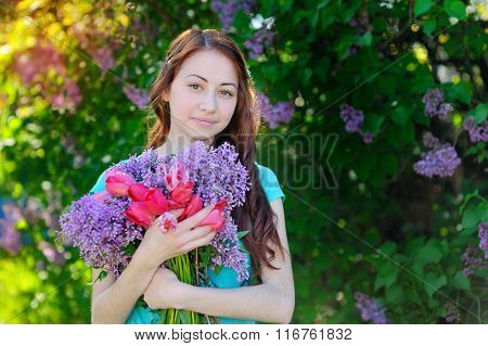 Beautiful Woman Holding A Bouquet Of Tulips And Lilacs