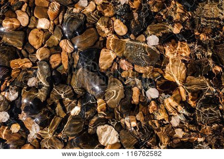 Colored Pebbles Under Water At The Coast