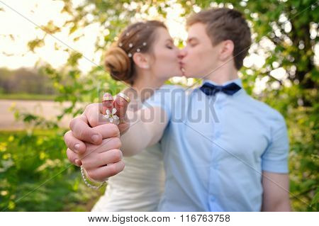 Bride And Groom Put Hands With Wedding Rings