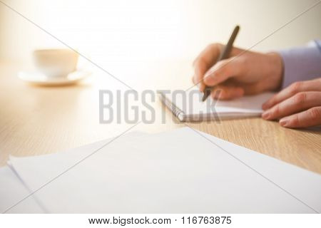 The male hand with a pen and the cup