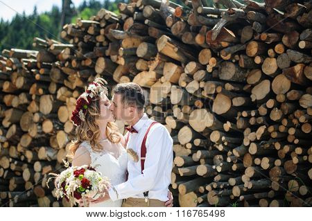 Bride And Groom Kissing On The Background Of Stacked Firewood
