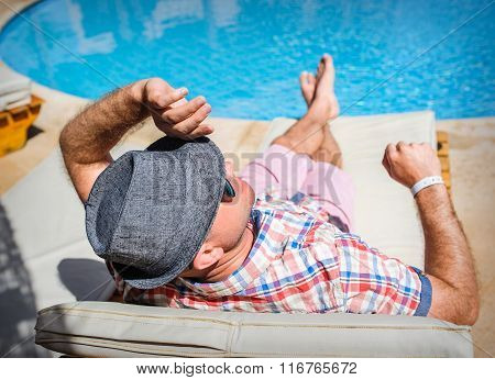 Happy man with a hat lying on a lounger