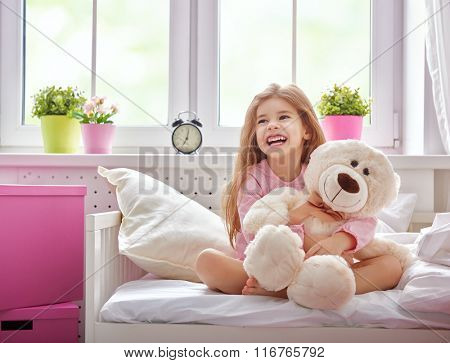 The child girl woke up and enjoys the morning sun. Girl laugh and hugs the teddy bear.