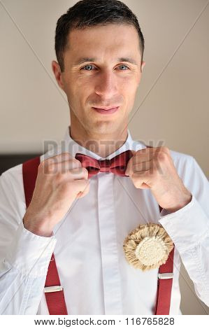 groom wears a red tie on a white shirt