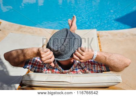 Man In A Hat Lying On A Lounger By The Pool