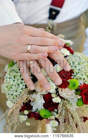 Hands Of The Bride And Groom On Bouquet
