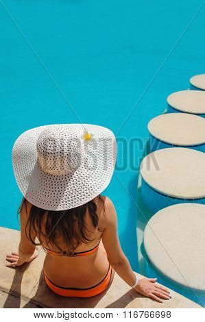 beautiful woman in a white hat sitting on the edge of the pool.