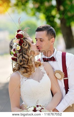 Bride And Groom Kissing On A Walk In The Park