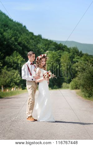 bride and groom walking on the road out of town